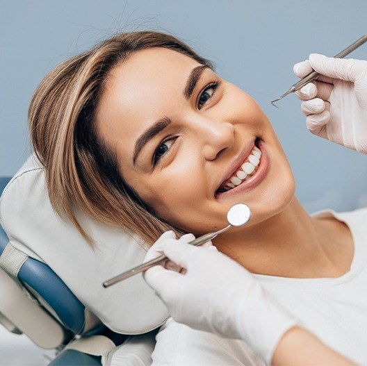 Smiling woman receiving dental treatment