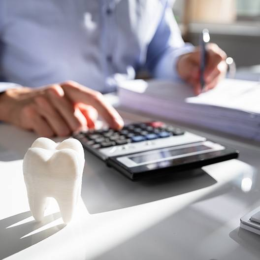 Man calculating the cost of dental treatment