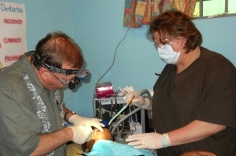 Dentist and dental team member treating patient