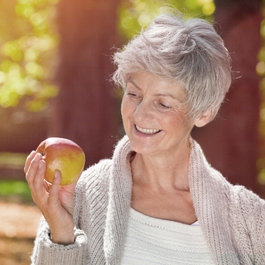 Smiling woman eating an apple after dental implant tooth replacement