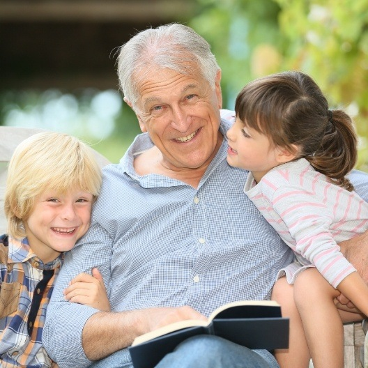 Older man with dental implant supported replacement teeth reading book to his grandkids